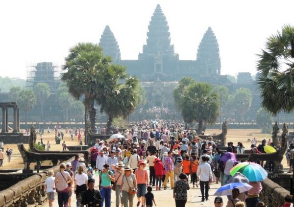 Столпотворение перед храмом Ангкор в солнечное зимнее утро. Более 400 гидов и тысячи туристов из всех уголков земного шара